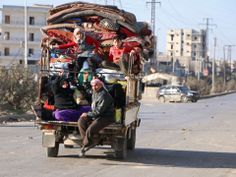 Syrians sit at the back of a truck loaded with belongings as they leave Aleppo in search of a safer area to call home.