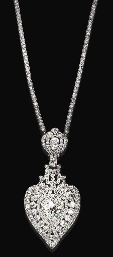 AN ATTRACTIVE BELLE EPOQUE DIAMOND PENDANT NECKLACE   Centering upon a detachable pavé-set diamond pierced openwork palmette motif pendant, enhanced by old European-cut diamond collets and a larger old European-cut diamond, suspended by a similarly-set foliate motif from an old mine-cut three-stone diamond link backchain, mounted in platinum (pendant may be worn as a brooch), circa 1925, 20¼ ins.