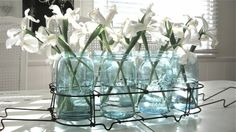 White irises in blue mason jars displayed in a simple wire rack. Very appealing.
