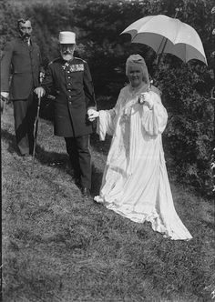 King Carol I of Romania holds hands with his wife Queen Elizabeth of Romania also known as Carmen Sylva as they walk on a grassy hillside early 20th...