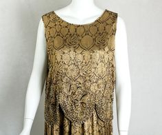 Beaded gold lamé dress, c.1924 The fabric is woven with a black-and-gold Deco pattern embellished with crystal seed beads and gold-tone bugle beads. The scalloped edges have embroidered accents of black-and-ivory silk floss. The geometric design uses curvilinear motifs—circles, ovals, and swirls. The skirt is attached to the slip, while the outer bodice shell is separate. Both pieces slip on without closures. The skirt is lined with plain gold lamé. Detail 5 Private collection