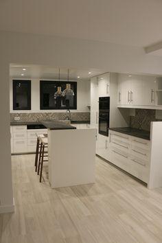Cuisine blanche, plan de travail gris effet béton, sol carrelage imitation plancher clair, crédence carreau de ciment