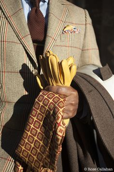 This unique chose of colors is sheer genius! Men's beige & light brown suit w/ wine & mustard windowpane stripes, accented w/ pale blue shirt, brown tie, mustard gloves. wine & mustard patterned scarf & light brown overcoat.