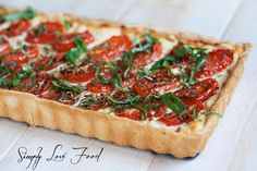 Tomato Basil Tart with Roasted Garlic Ricotta - Simply Love Food - pie crust, garlic, evoo, ricotta, parm, cherry tomatoes, sale, pepper, marjoram (?), oregano, rosemary and fresh basil.