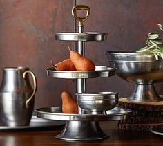 """Cavo Round Tiered Stand $73.99 Pottery Barn 25"""" diameter, 19.5"""" high 6"""" space in between tiers Made of stainless steel and brass."""