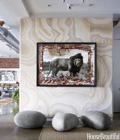 """A Peter Beard photograph hangs in the entry of a whimsical Manhattan loft. The felt """"boulders"""" are from VivaTerra, while the Sisal rug is by Stark."""
