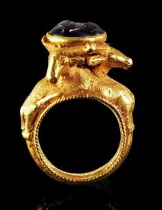 Greek Gold and Amethyst Ring, 1st Century BC Ring with 3 gazelles on the hoop holding an oval mounting with a carved amethyst depicting a female draped bust with stephané and cornucopia and corn ear.