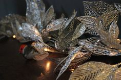 A beautiful Silver Leaf Fairy Light Garland.These are stunning LED lights, perfect for decorating your mantlepiece at Christmas! They have silver leavesin bunches; the leaves have lovely leaf skeleton detail giving them lots of texture. They have a lovely clear flex which is a generous length, making them more easily usable . They would look great across the mantle or along a lovely cottage windowsillMaaterial coated wire.. Comes complete with transformer plug.<strong>L:</strong>1550mm ...