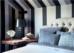 Cozy Transitional Bedroom by Antonio Martins - This contemporary bedroom with a sloped ceiling has a cozy feel, thanks to the wide-striped, black and gray striped wallpaper; it provides great depth perception while creating a dramatic backdrop. @Antonio Martins