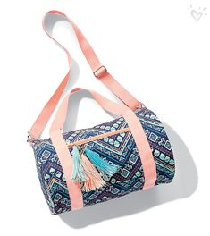 We love the pretty pop of coral on this print-perfect duffel.