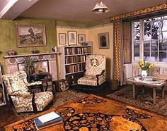 Shows a living room at Charleston. There is a patterned rug on the floor and two arm chairs and a book case sit either side of a fireplace