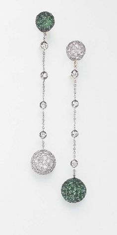 A PAIR OF DIAMOND AND EMERALD EAR PENDANTS Each pavé-set diamond or emerald boule, suspended by a diamond collet and oval link chain, to the surmount of similar design, mounted in 18k white and yellow gold.