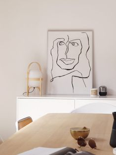 minimalist modern dining room with line drawing poster by mette handberg via hege in france. #linedrawing #art #artwork #drawing #portrait #france #minimalistmodern #diningroom #diningtable #whitecabinet #whitesideboard #sideboard #mettehandberg