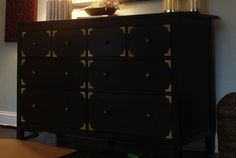 She used painter's tape (spray painted gold) to add faux brackets to this Ikea dresser.  I would like to do that using a stencil!