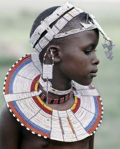Africa | A Maasai girl in traditional attire.  The predominant white colour of her beadwork and the circular scar on her cheek donate that she is from the Kisongo section of the Maasai, the largest clan group, that lives either side of the border in Kenya and Tanzania | © Nigel Pavitt