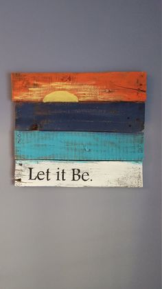 Let it be with sunset rustic wood sign made from reclaimed pallet wood. Wood is painted white, turquoise, navy blue and orange with a yellow