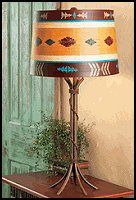 hand-painted southwestern shade in warm red, turquoise and gold tops the solid steel Southwest Iron Braided Table Lamp with braided wire rope in a rust finish.