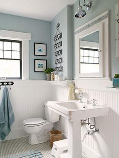 To reinforce the bath's period style, the homeowners added thick trim above the wainscot and swapped in a salvaged pedestal sink. Sconce: Pottery BarnPaint: Behr's Flint Smoke (walls) and Absolute White (trim)