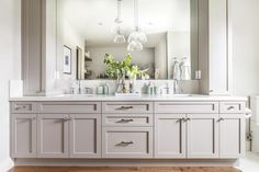 A light gray shaker vanity accented with nickel hardware and a white quartz countertop is fitted with his and her sink paired with polished nickel gooseneck faucets.