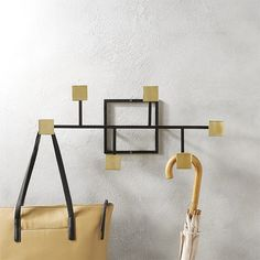 Shop rise and fall coat rack.   Abstract grid lines up a modern piece of art that doubles as everyday storage.  Handmade linear frame supports six shiny square knobs at varying heights to accommodate coats, bags, hats and more.