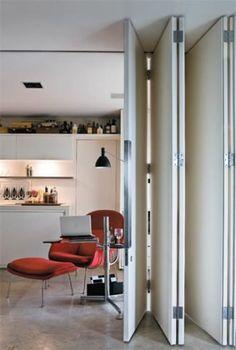 Canto de leitura integrado à sala. No projeto da arquiteta Roberta Martins, quando chegam hóspedes em casa, a porta camarão se fecha e o espaço volta a ser quarto. Onde encontrar: a poltrona Womb Chair, de Eero Saarinen, é da Micasa, e a luminária de pé Bauhaus 90, da Lumini. Limestone Blue Marine, da Mont Blanc.