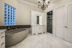 Yes, please to this master bath // Dual white vanities, marble countertops and tile, standalone stone tub, glass shower and a chandelier to top it off