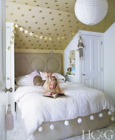 Daughter Amaya reads on a bed from Canvas Home, which is topped with a Plum & Bow Alia duvet. Osborne & Little's Coronata Star wallpaper covers the ceiling.