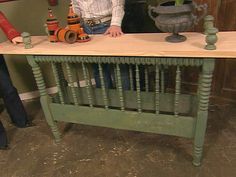 A console table is made out of an old bed frame. The tops of the four bedposts are cut off making each piece of the frame level. The tabletop is then fastened to the frame. The pieces that were cut off are made into finials and attached to the tabletop.