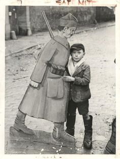 1944- Once used as a target in a German shooting gallery in Metz, a cardboard model of a Russian soldier now acts as a toy for little French boy.