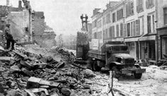 US Third Army Engineers clear up debris from the streets of battle-scarred Saarlautern, Germany, while a soldier watches for snipers. December 1944 ~