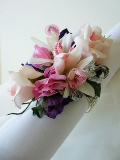 Wrist corsage made on a diamante bracelet featuring mini cymbidium orchids, pastel pink roses, purple and pink sweet peas with silver braid trim.  Ideal for Mother of the Bride/Groom, Bridesmaids, Prom, Dinner Dance or cruise wear.