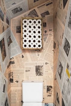 Awesome bathroom with newspapers as wallpaper and toilet rolls stock in a crate