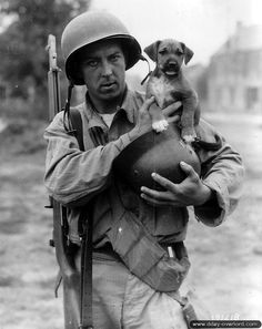 U.S. Army Pfc. Joseph E. Day holds a German helmet he has taken as a war trophy and a stray puppy he has adopted and named Invasion during the Battle of Normandy, France, June 1944.