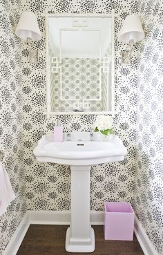 Whimsical powder room with cream and black wallpaper paired with pink bathroom accents. White faux bamboo mirror with Greek key trim sits above glossy white pedestal sink. Polished nickel sconces flank white bamboo mirror and pink lacquer trash can sits on stained oak wood floors.