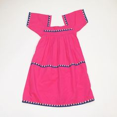 Pink dress with sleeves decorated with peach and blue pintas. Handmade by the Ngäbe-Buglé woman of Panama.