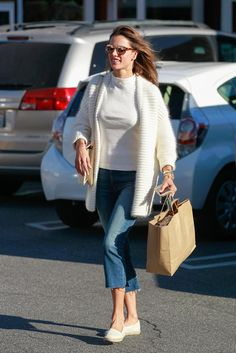 Alessandra Ambrosio wearing Mophie Juice Pack Rechargeable External Battery Iphone Case in Gold, M2malletier Memento Mori Bag, Maje Menphis Oversize Knit Cardigan, French Connection Ronit Ribbed High Neck Top and Mother Insider Crop Step Fray Jeans in Not Rough Enough