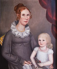 In the hall and opposite the Maentel family group hang two portraits by Ammi Phillips, that of a Mrs. Robinson, circa 1819 (not seen here), and a portrait of Mrs. William Northrop Bentley and her daughter, Louisa, painted circa 1815-1818. Few double portraits by Phillips have been found, and the daughter holding a slice of watermelon is a show stopper. Louisa was an adult when her husband, Edwin Griggs, ran off to join the Gold Rush in 1848; she never saw him again. It is details like this…
