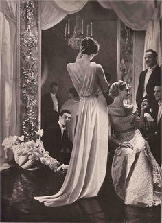 """12-12-11  Harper's Bazaar May 1935   """"Ten O'clock in the corner of the drawing room and, seated, a listener in Jean Lanvin's heavy, rich pink brocaded taffeta with a decolletage quilted in silver lame. The other dress is Lelong's Grecian """"Tita,"""" its sweep of pure white crepe gathered into a drawstring belt."""""""