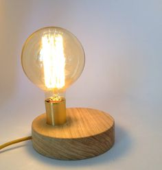 This is a handmade minimal table lamp.  The round base is a hand – turned piece and is made of natural Oak tree wood.  There is a round hole on the wooden base where a metal cup in gold is adapted. Inside the metal cup is installed a Bakelite bulb socket.  The lamp is wired with a textile cable in gold color.  A white on/off switch and a two-pin European plug are installed on the cable (Table lamp use).  Takes any normal E26-E27 light bulb max 60W or any LED light bulb.   This a stylish ...