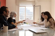 Group of people working in office by Milles Studio for Stocksy United. Group of people working in office Stylish women and man sitting at table in office and brainstorming on architect plan.