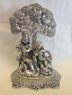 Statue of white metal Radha Krishna with flute under tree