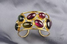 Fine Jewelry - Sale 2539B - Lot 476    18kt Gold Gem-set Cuff Bracelet, Prince Dimitri, bezel-set with green, blue, and pink tourmaline cabochons, within an openwork frame, 48.8 dwt, interior cir. 6 1/2 in., signed.     Very good condition, minor wear and few scratches, tourmalines are medium to medium-dark in color, inclusions are visible within stones, cuff open at the back.  Sold for $5,333.00