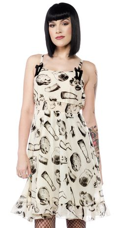 SOURPUSS DOLL PARTS DRESS - Our new Doll Parts Dress was made with the macabre lady in mind. This soft, flowy, chiffon dress has an amazingly creepy doll parts print and is detailed with two black bows on adjustable straps. The waist is super stretchy, so not only is it comfy it's really flattering too! There is a slight pink tint to the cream chiffon, which is hard to capture in photos. Psst... This is a very sheer dress, so keep that in mind when picking out your undies for the day! ;)