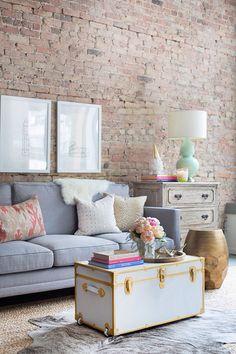 sala rústica e vintage, com parede de tijolinhos e mala antiga como mesa de centro