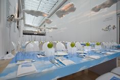 <p> Images of blue skies decked the tabletops, and green apples sat atop Lucite boxes that glowed after the sun...