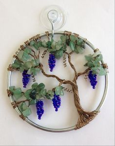 """Grape Vine Sun Catcher  This Grape Vine Sun Catcher is an original, MyTwistedArt design. This particular design has never been done by anyone else.   Foliage: Light Aventurine semi precious chip beads Grapes: Sapphire Luster mix glass seed beads Wire: Silver & Antique brass Size: 3""""H X 3""""W   Sun Catchers are handmade using twisted wire, stone chip beads, glass E-beads, glass seed beads or other types of beads. Their true beauty will shine through when hung in your window in the sunshine. ..."""