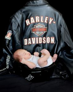 Harley Davidson baby in daddy's helmet with daddy's jacket in background.