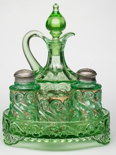 "Five-piece ""S-Repeat"" Condiment Set,  apple green, comprising a cruet with original stopper, pair of shakers, toothpick holder, and circular tray. National Glass Co. and Dugan Glass Co. First quarter 20th century."