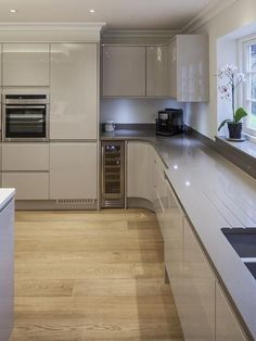 The simplistic modern kitchen: white plastic units, grey countertop, wall oven and wooden floors. - The simplistic modern kitchen: white plastic units, grey countertop, wall oven and wooden floors. Home Decor Kitchen, Rustic Kitchen, Kitchen Interior, New Kitchen, Kitchen White, Kitchen Ideas, Grey Gloss Kitchen, Kitchen Inspiration, Modern Kitchen Cabinets