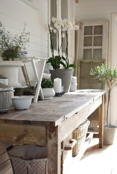 Beautiful unfinished reclaimed wood table at counter height to serve as a gardening/potting station.  Sweet perfection